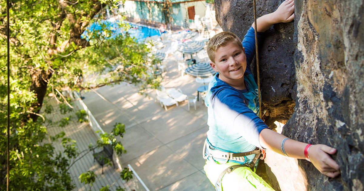 Photograph of a youth climbing inside Crawdad Canyon with the Veyo Pool swimming pool in the background.