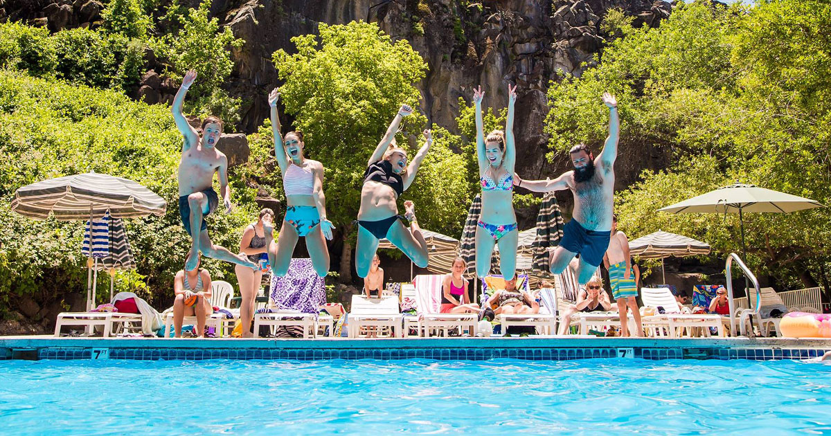 Swimmers jump theatrically into Veyo Pool with Utah red rocks in the background.
