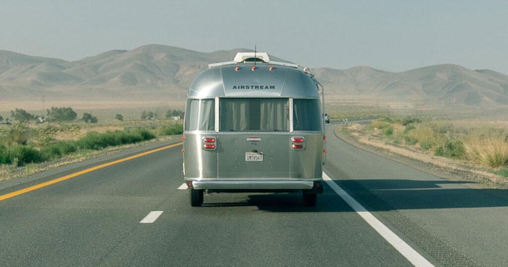 An airstream RV driving through southern Utah.