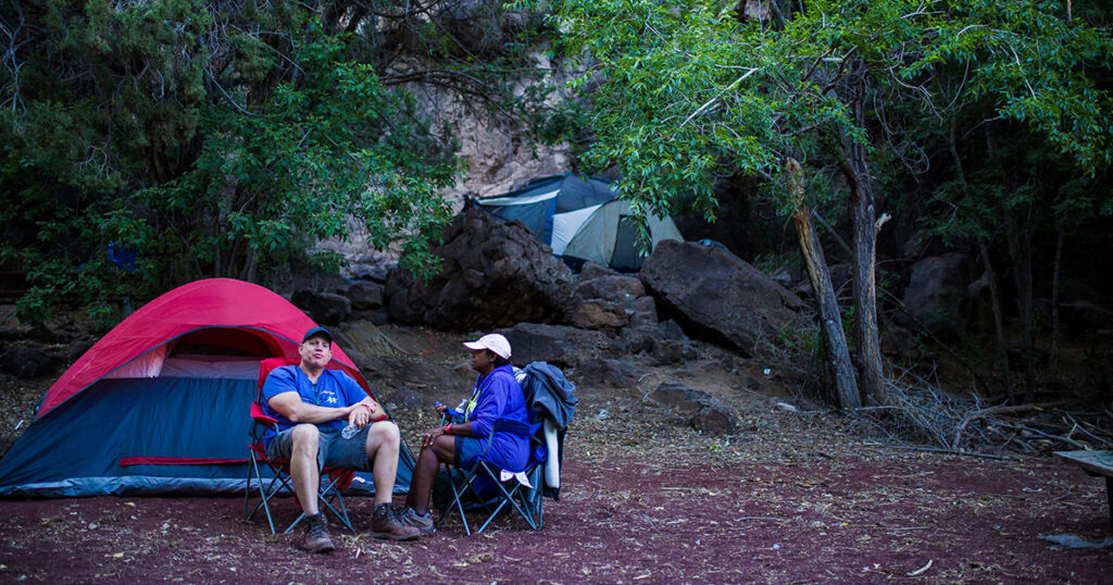 Campers relaxing near their tent at Veyo Pool.