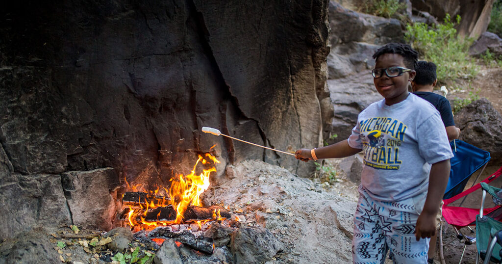 A young camper roasts a marshmallow over an open-air fire pit.